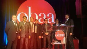 Group on men in suites smiling on stage after receiving award