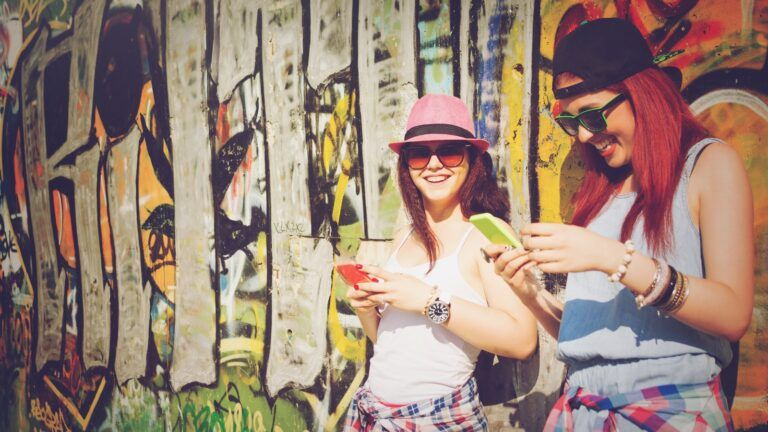 two girls leaning on graffiti looking at phones