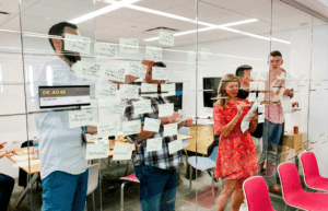 A team using a glass window to ideate with various sticky notes