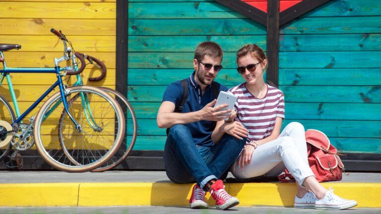 Couple looking at phone sitting on curb