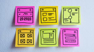 A set of sticky notes on a wall, with application wireframes drawn on them in marker