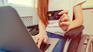 A woman in a wheelchair holding a credit card as she uses a laptop